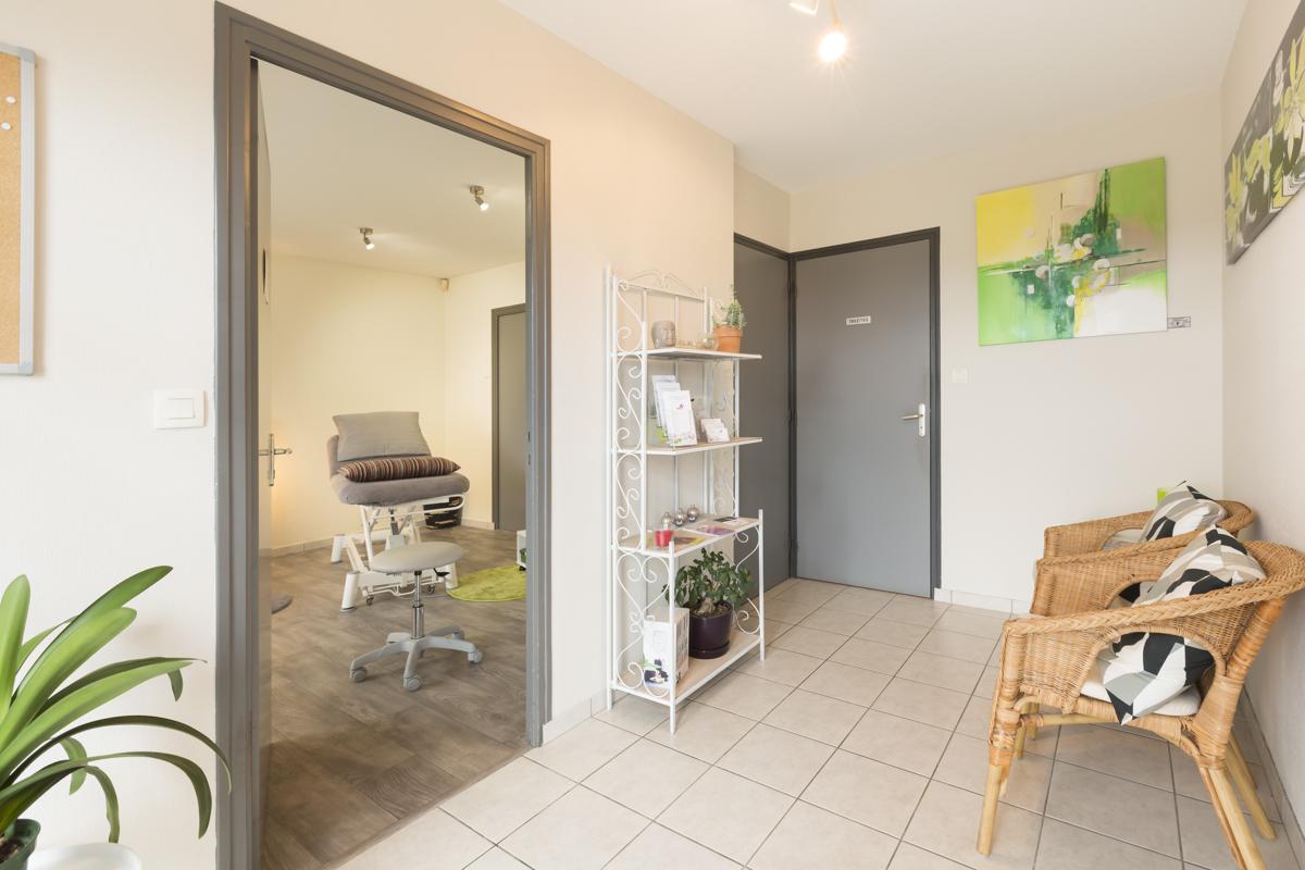 photo de l'entrée du cabinet avec un sol carrelé et 2 fauteuils faisant face à la porte ouverte sur la table de massage