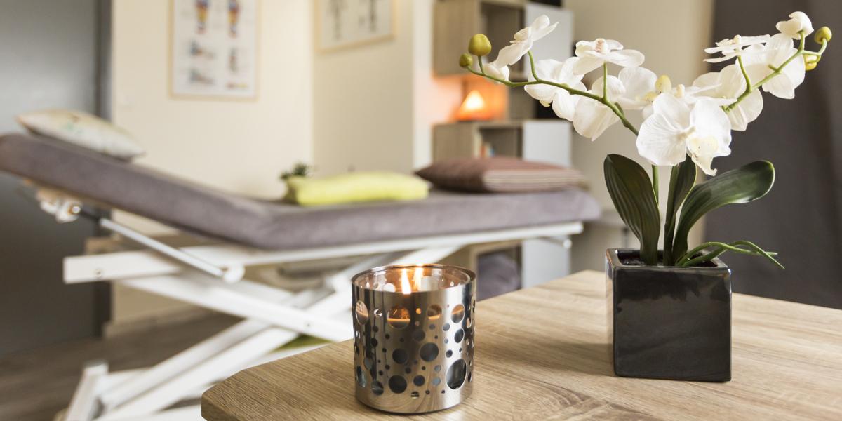 Fleur et bougie avec table de massage en arrière plan